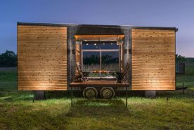 "Meet the Tiny House Alpha from New Frontier Tiny Homes. It is 24 feet long and 102"" wide. The garage door adds a nice effect but one can only wonder how it could not possibly get in the way when the door is open. The bathroom has a Jacuzzi tub. Now that is some fancy living!"